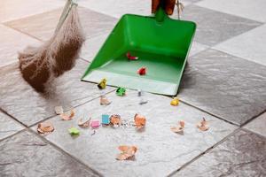 sopa upp rester av pappersgolv med en kvast och en soptunna. foto