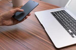 handen med smartphone vid skrivbordet foto