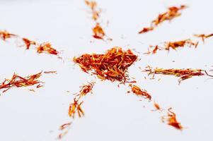 selektivt fokus närbild röd saffran i form av mandala med hjärta på vit bakgrund. känsliga blomtrådar. naturlig hälsosam krydda. för kafémeny eller katalog foto