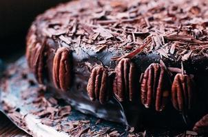 makrovy av hela mörk chokladkaka med vacker glasyr, chips och pekannötter på sidan på metallskålen. selektivt fokus. lyxig glasyr. bild för meny eller konfektkatalog foto
