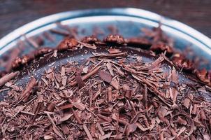 makrovy av utsökt mörk chokladkaka med vacker glasyr och pekannötter på sidan på det bruna träbordet. selektivt fokus. lyxig glasyr. bild för meny eller konfektkatalog foto