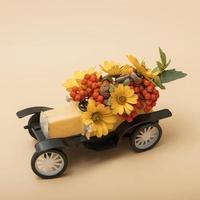 dekorativ höstkomposition av en leksaksbil med rönn, blommor foto