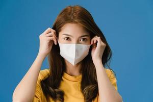 ung asiatisk tjej som bär medicinsk ansiktsmask på blå bakgrund. foto