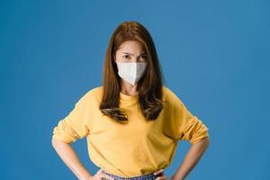 ung flicka bär mask med negativt uttryck på blå bakgrund. foto
