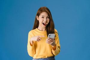 ung dam som använder telefon med positivt uttryck på blå bakgrund. foto