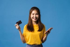 ung asiatisk dam med telefon och kredit bankkort på blå bakgrund. foto