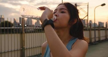 Asien idrottsman dam övar dricksvatten efter att ha sprungit i urban. foto