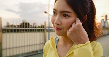 asien idrottsman dam övningar med smartphone för att lyssna på musik. foto