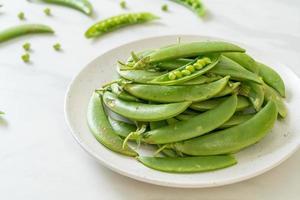 färska söta gröna ärtor på tallrik foto