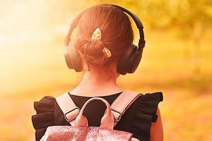 flicka bär hörlurar. hörlurar med trådlös teknik. foto