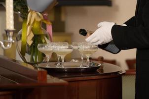 en bricka med glas champagne och en flaska mousserande vin. foto