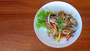 ovanifrån av spaghetti med kryddig blandning skaldjur i vit tallrik. foto