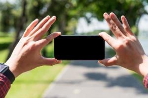 närbild manliga händer som håller smartphone för att ta foto. foto