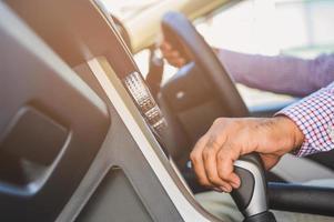närbild manlig hand kör bil som flyttar växellåda. foto