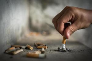 hand släcka en cigarett, cigarett rumpa foto