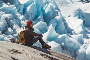 resenär man sitter på en sten på bakgrunden av en glaciär och snö foto