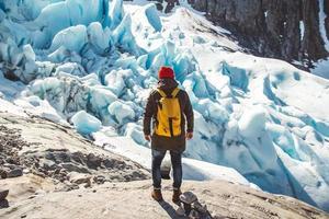 resenär man står på en sten på bakgrunden av en glaci foto