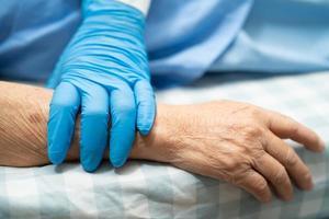 läkare som håller rörande händer asiatisk senior kvinna patient med kärlek foto