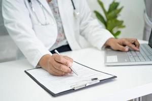 läkare skriver hälso medicinsk anteckning i urklipp med bärbar dator på sjukhuset. foto