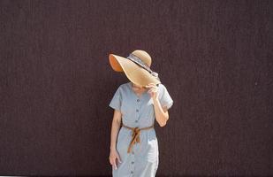 porträtt av en vacker kvinna i elegant sommarhatt på lila vägg foto