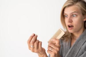 chockad kvinna som borstar håret som lider av håravfall foto