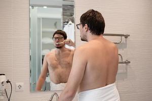 en ung man borstar tänderna i badrummet foto