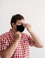 ung man som tar på sig en skyddsmask foto