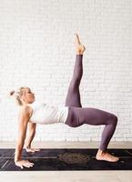 blond kvinna som utövar yoga hemma, gör glute bridge foto