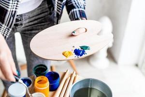 närbild av kvinnliga konstnärshänder som blandar färger på träkonstpalett foto