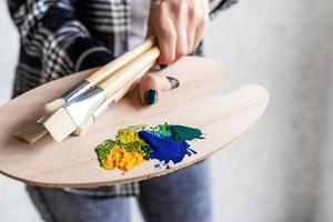 närbild av konstnärshänder som håller träkonstpalett och penslar foto