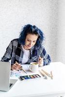 designer som arbetar med färgpaletter och bärbar dator i hennes studio foto