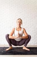 blond kvinna som utövar yoga hemma foto