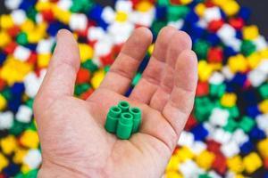 hand med färgglada plaststenar på en färgstark bakgrund foto