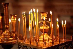 många långa brinnande ljus under gudstjänsten foto