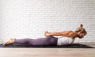 ung attraktiv kvinna som utövar yoga, bär sportkläder foto