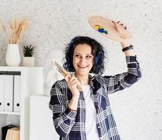 kvinnakonstnär i hennes studio som håller konstpalett och penslar foto