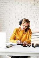 kvinna som studerar online med hjälp av bärbar datorhandstil i anteckningsboken foto