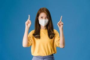 ung asiatisk tjej som bär ansiktsmask visar något på tomt utrymme. foto