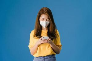 ung asiatisk tjej bär ansiktsmask med mobiltelefon på blå bakgrund. foto