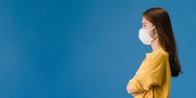 ung asiatisk tjej bär ansiktsmask titta på tomt utrymme på blå bakgrund. foto