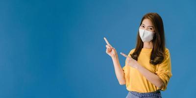 ung asiatisk tjej bär medicinsk ansiktsmask visar något på tomt utrymme. foto