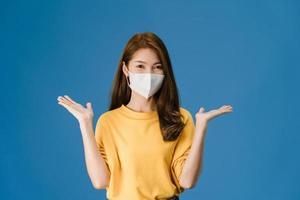 ung asiatisk tjej bär ansiktsmask som visar fredstecken på blå bakgrund. foto