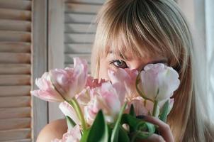 kvinna som gömmer sig bakom blommor foto
