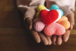 blandade färger garn hjärta på att ge händer foto