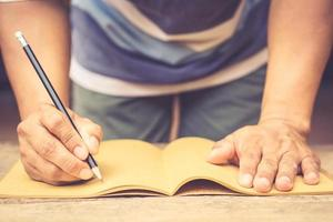 manlig hand som håller penna och skriver anteckningsbok på gammalt träbord foto