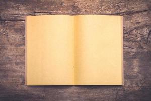 öppen bok på gammalt träbord foto
