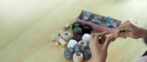 brodera sömnad med kvinnans hand. hantverksarbete och kvinnliga händer. foto