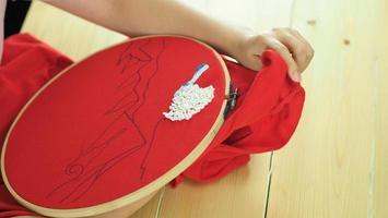 kvinnahänder och hantverksarbete. brodera söm för hand. foto