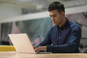 ung asiatisk affärsman som arbetar med bärbar dator på kontoret. foto