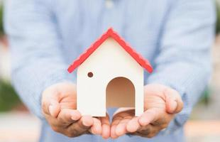 hand som håller ett mockuphus. fastighetslånförsäkring foto